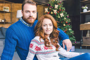 Couple sitting in christmas decorated room