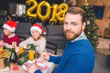 Father sitting at christmas table with kids