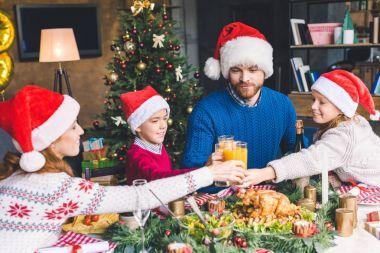 Family clinking glasses on christmas dinner