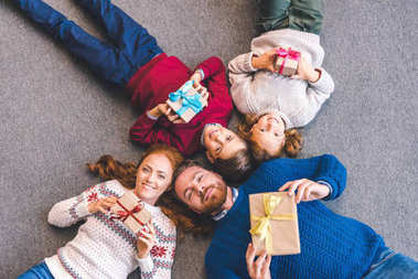family laying on floor with gifts