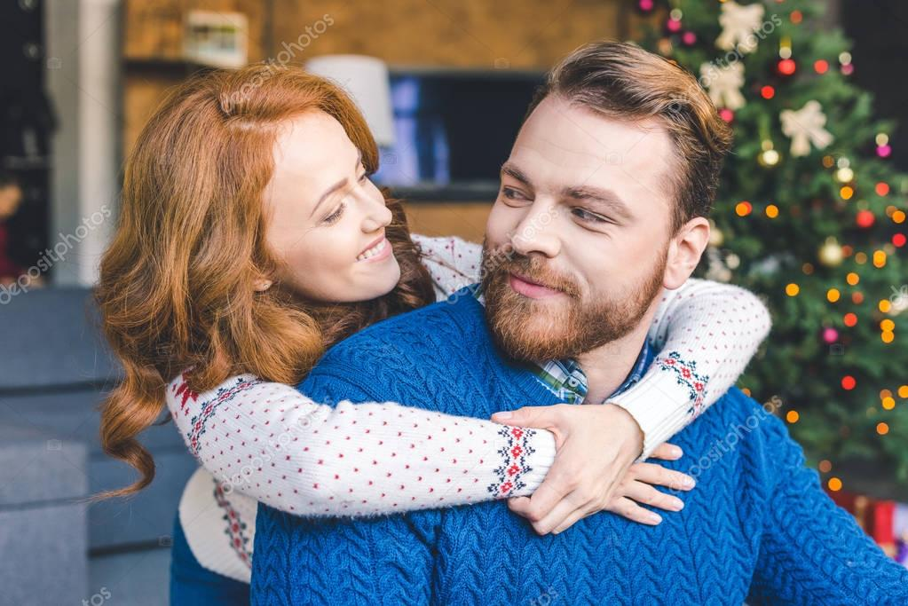 couple in warm sweaters embracing