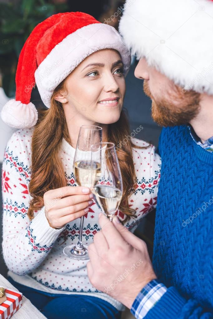 couple clinking champagne glasses on christmas