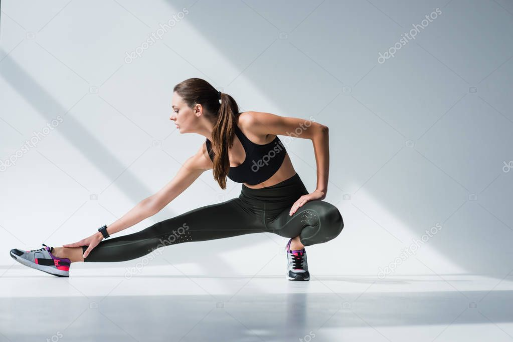 sporty woman stretching legs