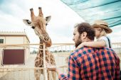 family looking at giraffe in zoo