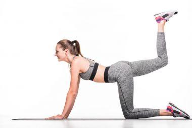 Sportswoman exercising on yoga mat