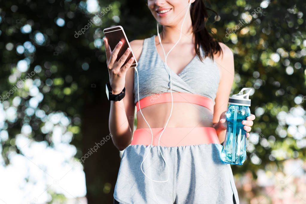 sportswoman in earphones using smartphone