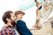Fotografia famiglia alimentazione giraffa in giardino zoologico