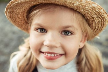 Portrait of smiling little girl in straw hat looking at camera stock vector