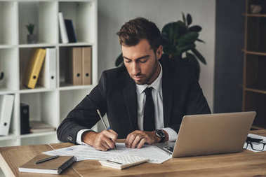 Young handsome businessman doing paperwork in modern office stock vector