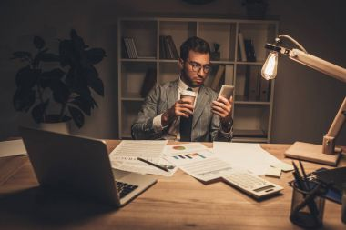 Businessman with coffee using smartphone