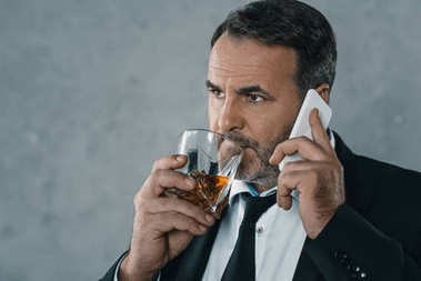 businessman talking by phone with whiskey