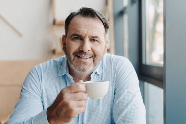 Smiling mature businessman with cup of coffee looking at camera stock vector