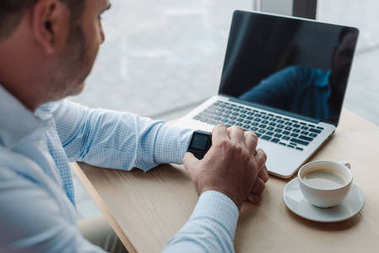 Businessman checking time on smart watch
