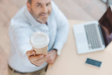 Businessman showing disposable cup of coffee