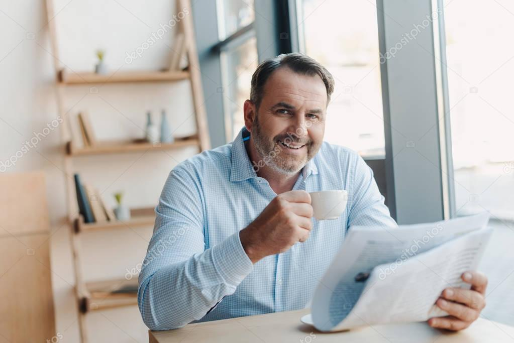 businessman drinking coffee with newspaper