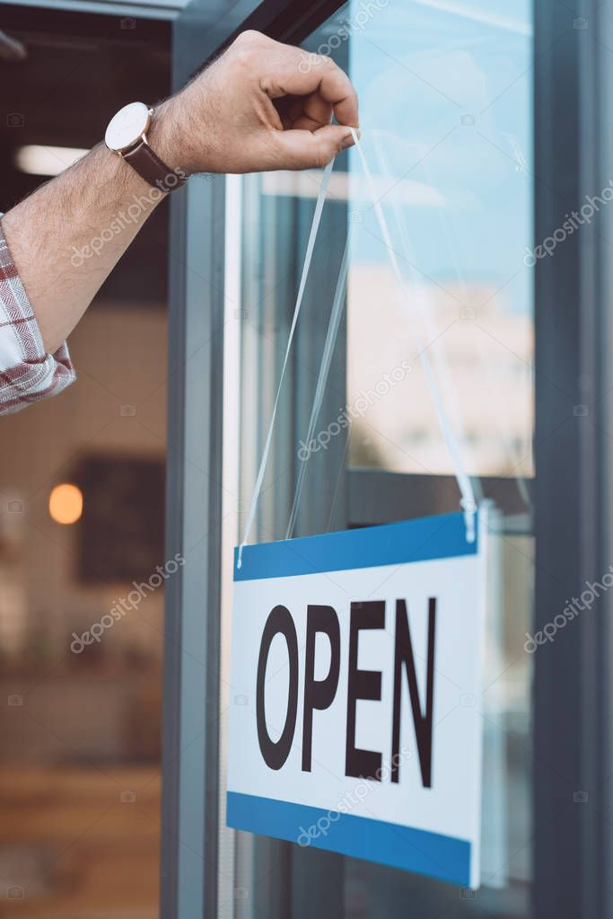 man hanging open signboard