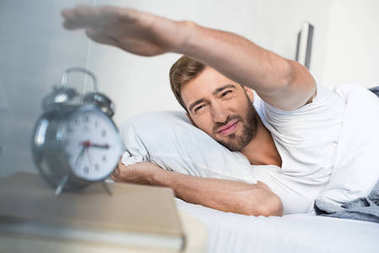Sleepy young man in bed reaching to turn off the alarm clock stock vector