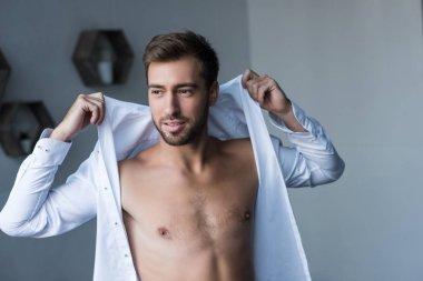 man putting on shirt