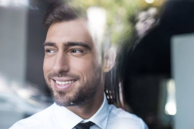 Smiling businessman looking out window