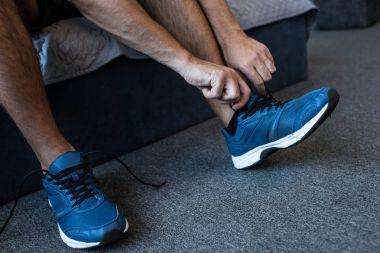 man tying laces on sneaker