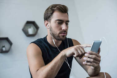 Athletic man using smartphone
