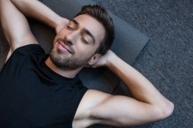 man on yoga mat with eyes closed