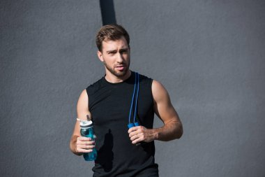 sportsman with skipping rope and water bottle