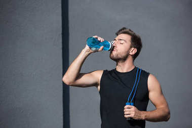 man with skipping rope drinking water
