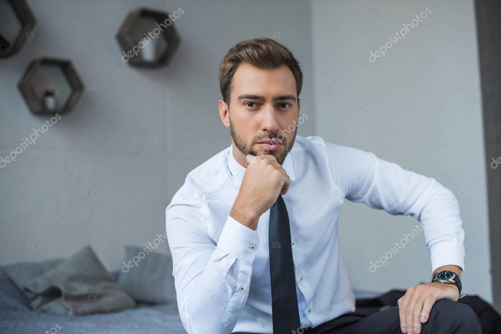 Handsome young businessman in formal wear sitting on bed and posing with hand on chin