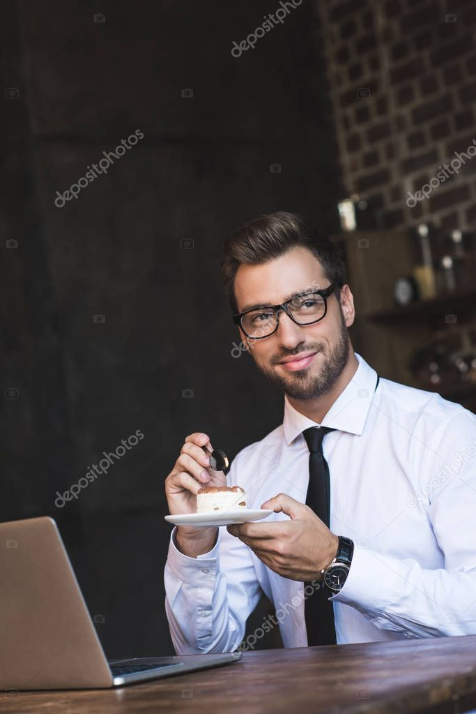 businessman eating cake at cafe