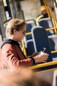 člověk používající smartphone v autobuse