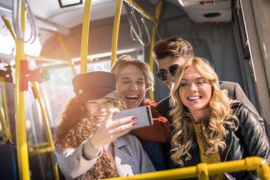friends taking selfie in bus