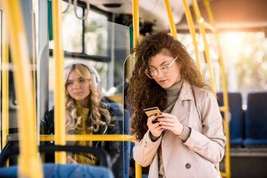 girl using smartphone in bus