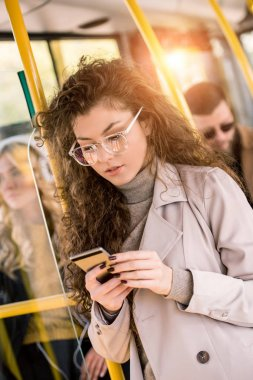 girl using smartphone in bus