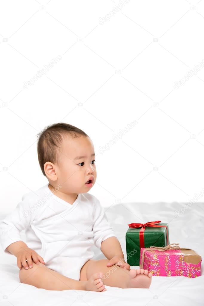 asian toddler and wrapped presents