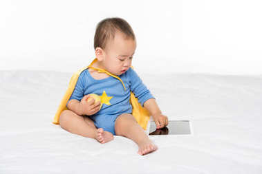 asian toddler with apple and tablet