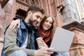 Fotografie couple using laptop on street
