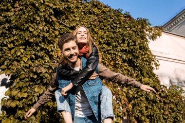 couple piggybacking in autumn park