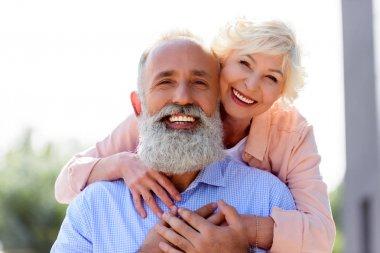 Portrait of happy senior woman hugging husband stock vector