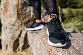 Frau in Joggingschuhen steht auf Felsen