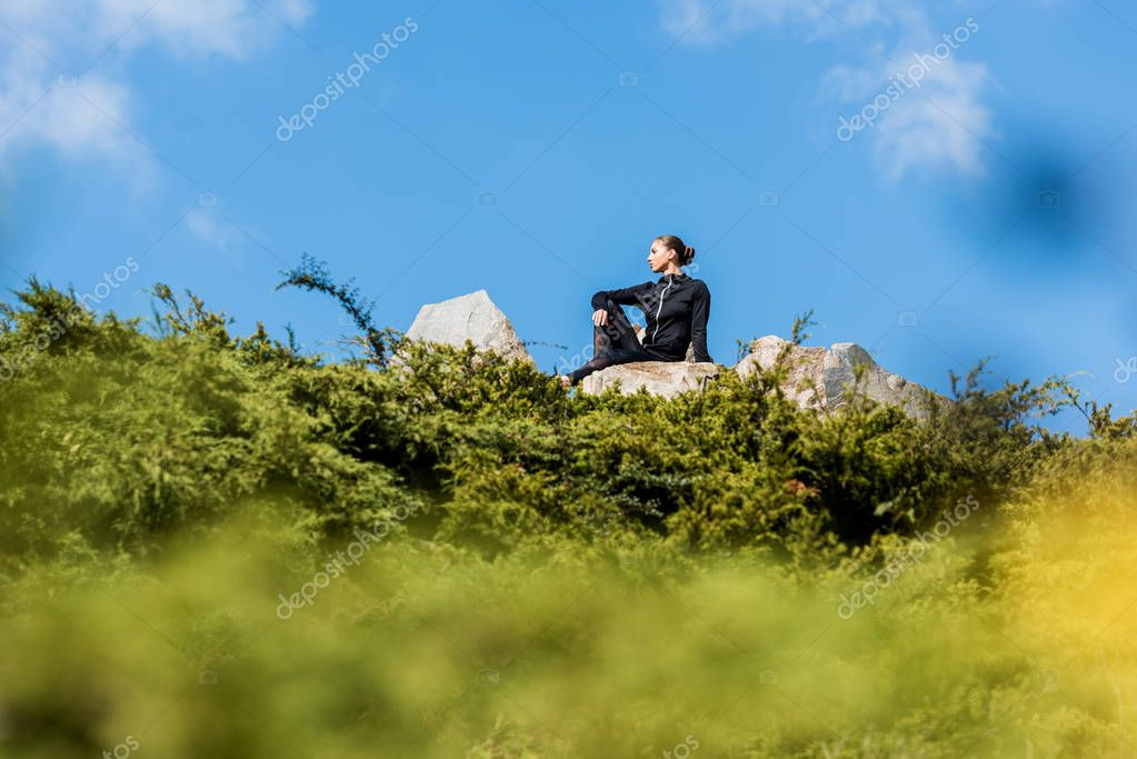 woman sitting on rocks