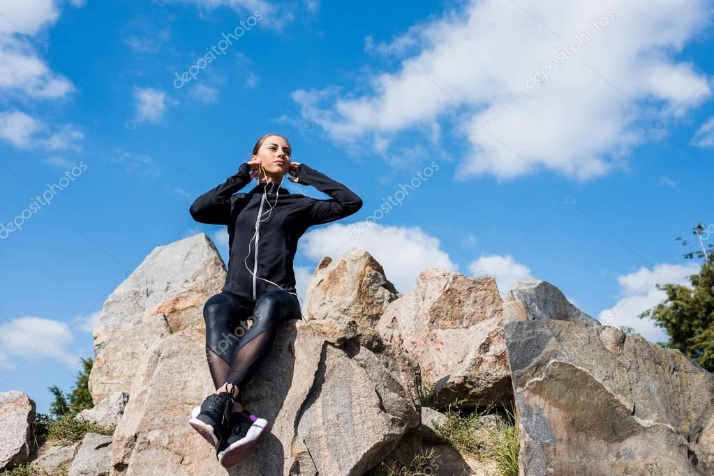 woman sitting on rocks and listening music