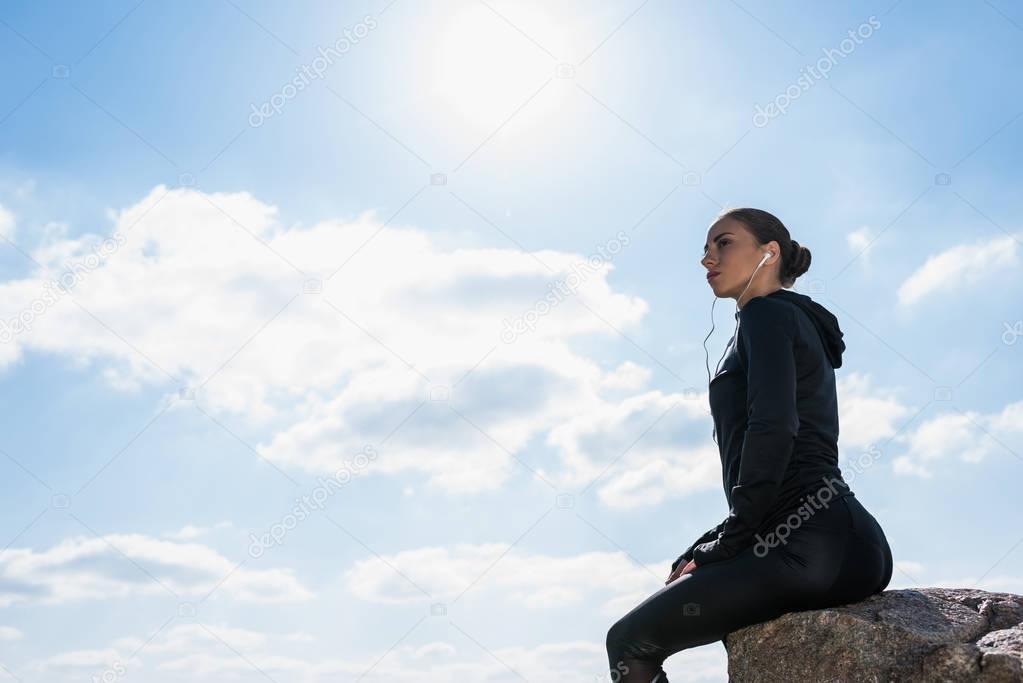 sportive woman sitting on rock