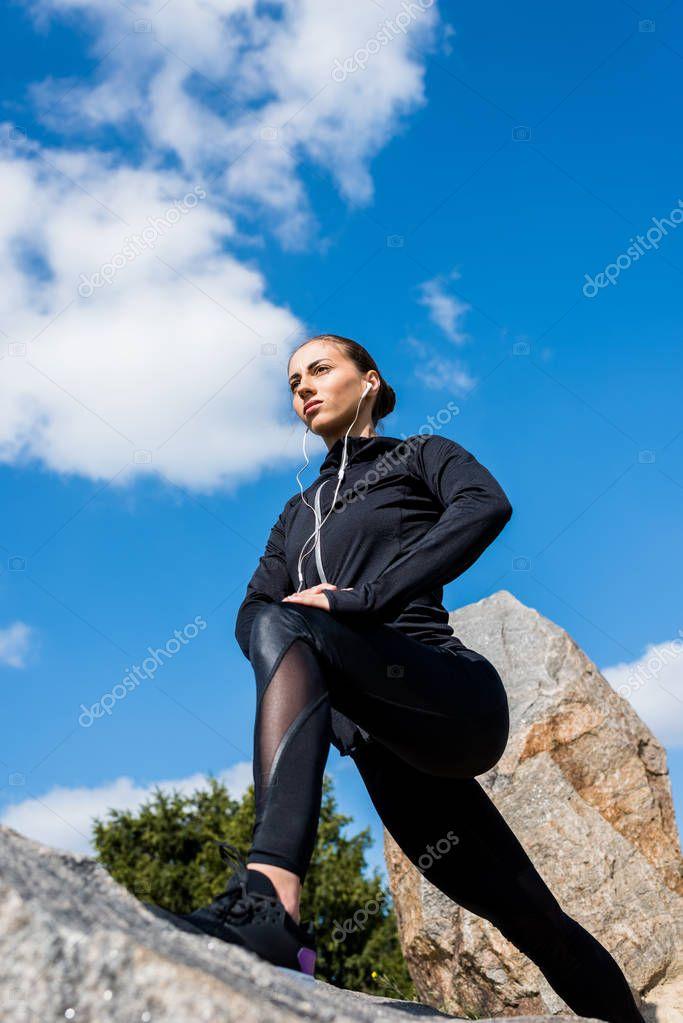 woman stretching legs on rocks