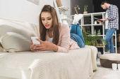 Žena na pohovce s smartphone