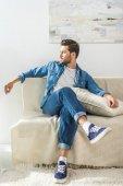 attraktiver Mann sitzt auf Sofa