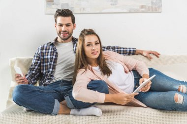 Couple on sofa with devices