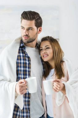 Young attractive couple having coffee while being wrapped in plaid stock vector