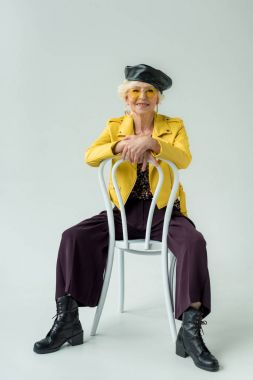 fashionable senior woman sitting on chair