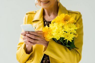 senior woman with flowers and smartphone